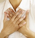 woman's hands over heart